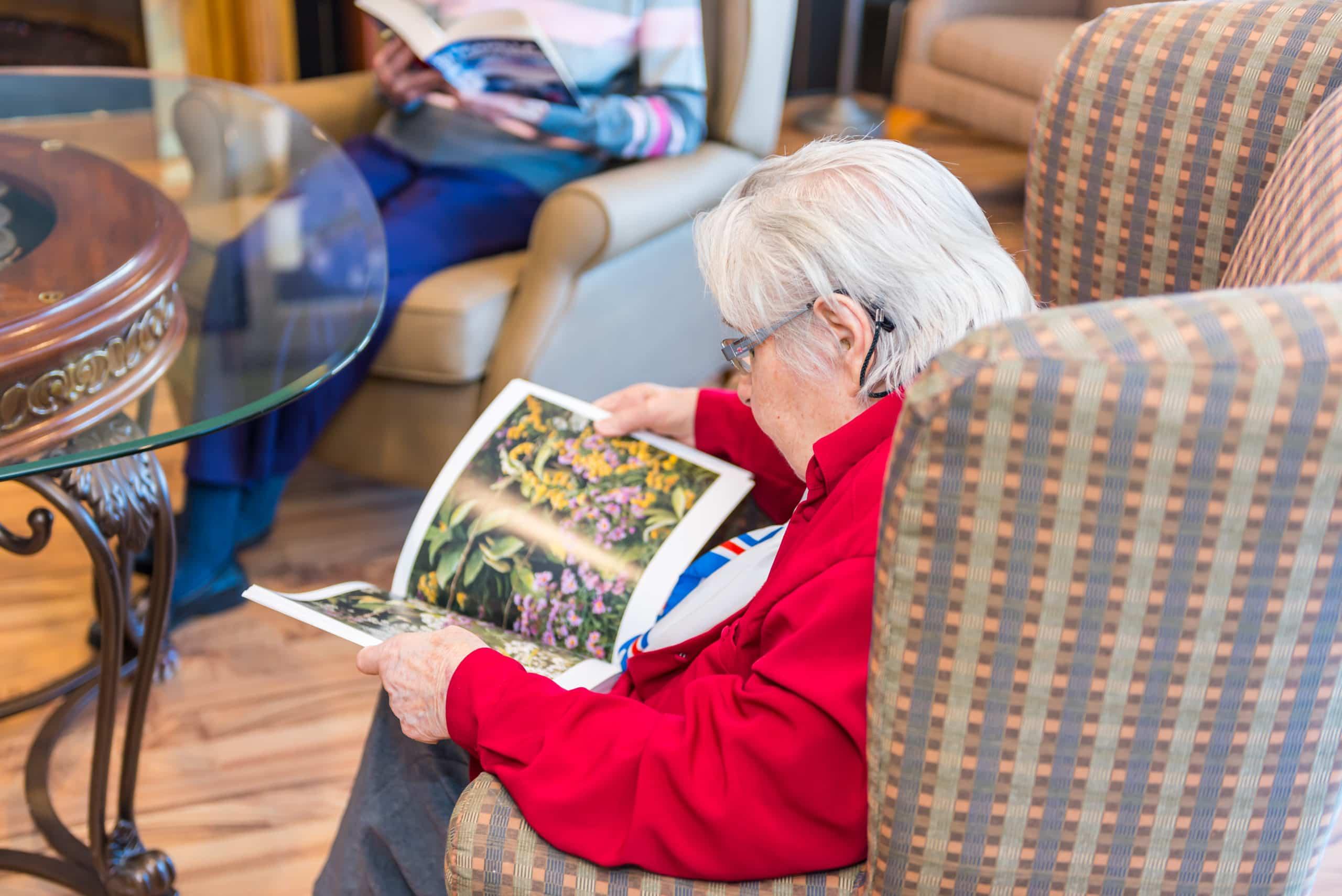 Senior woman reading in Bennett Centre recreation room